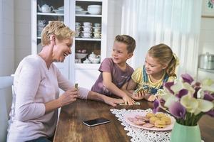 Moeder met zoontje en dochtertje-spelen aan keukentafel