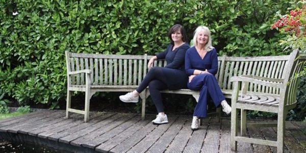Gera en Marieke zitten op een tuinbank in een park