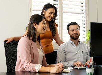 Drie jongvolwassenen kijken naar een beeldscherm