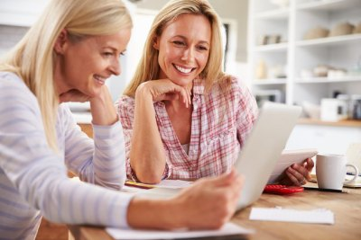 Twee vrouwen aan de keukentafel met laptop en tablet
